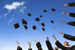 students-throwing-graduation-hats-air-celebrating-blue-sky-38965076